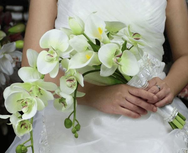 Свадебный букет из орхидей в руках у невесты